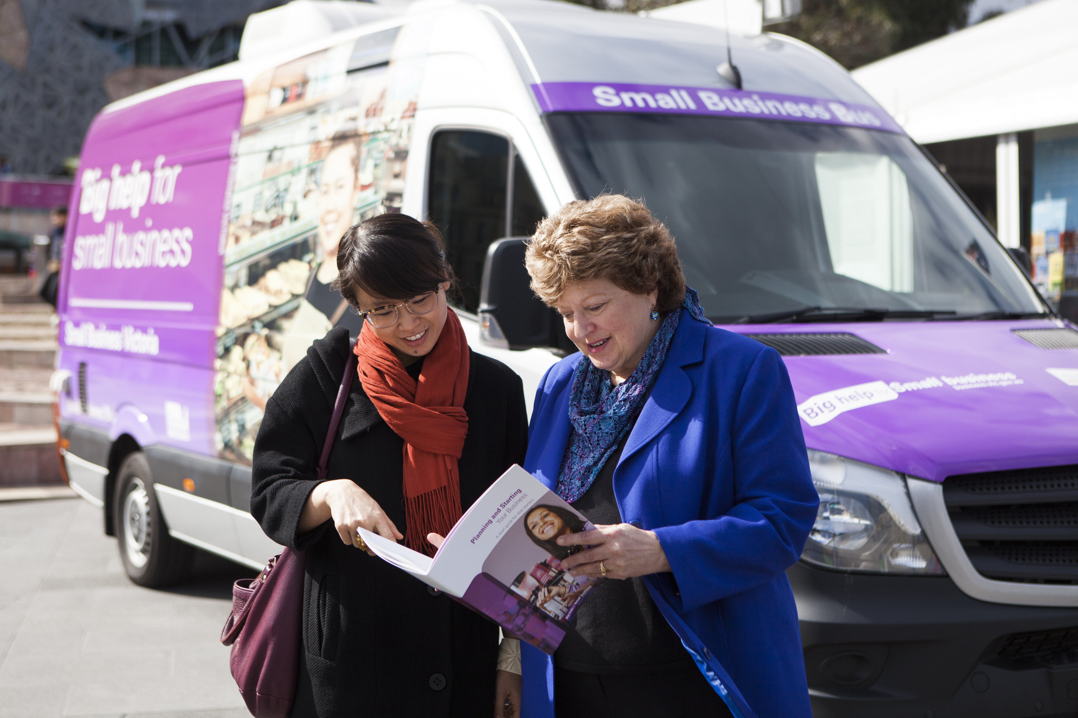 Two ladies looking at a business book outside the small business bus